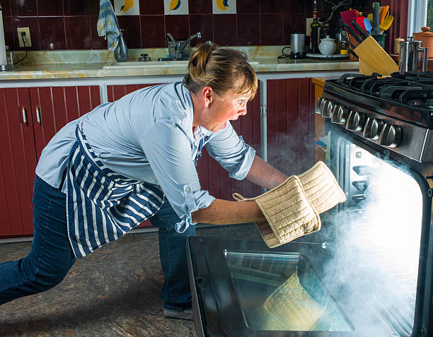 Mature woman shocked at oven fire in kitchen. stock photo
