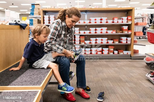 Mature caucasian woman shopping for shoes for her son  in a department store