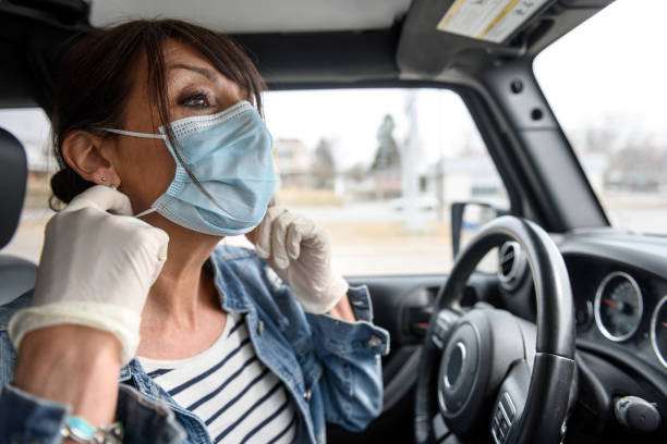 Mature woman shopping grocery, removing mask in the car stock photo