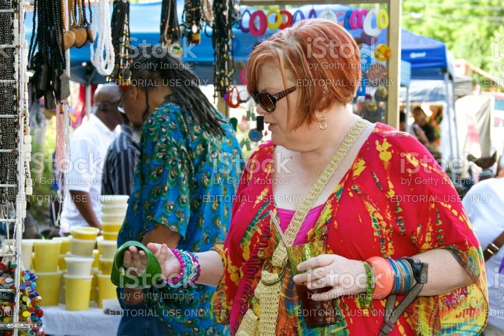 Mature woman shops for handcrafted jewelry at an outdoor African-American Art Fair stock photo