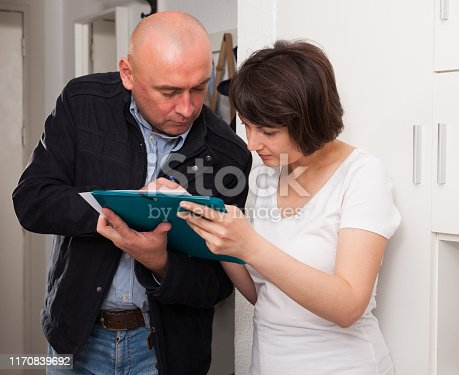 istock Mature woman signing papers with social worker at home 1170839692