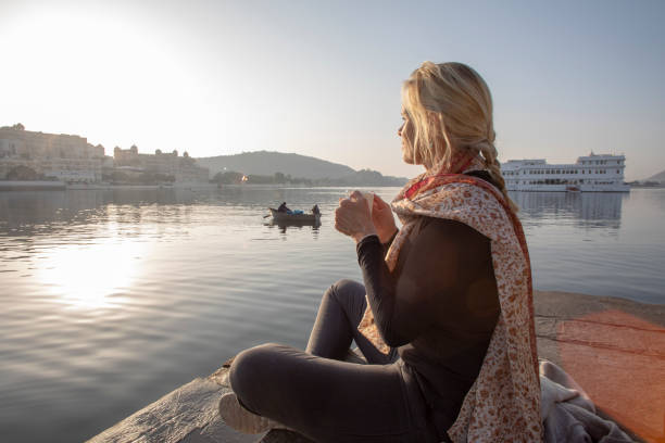 Mature woman sits on a ghat at sunrise with a hot beverage, looks out across lake Lake Pichola, Udaipur lake palace stock pictures, royalty-free photos & images