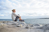 Mature woman sitting alone on rocks, looking at view