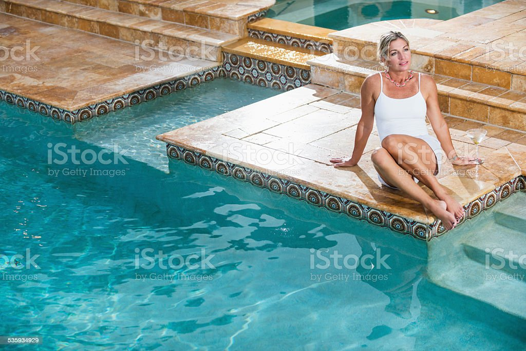 Mature woman sitting at the edge of a swimming pool stock photo