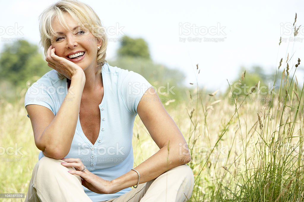 Mature woman sitting in countryside stock photo