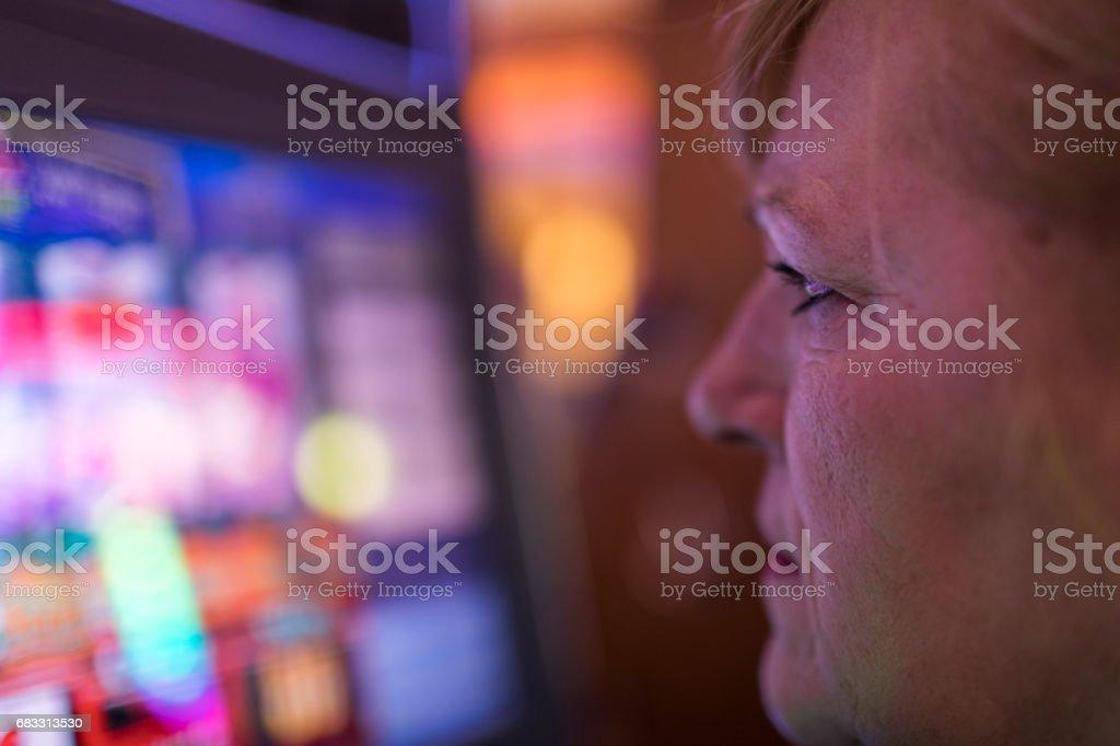 En mogen kvinna, sitter framför en spelautomat, är allvarligt att kontrollera skärmen medan spelande i Las Vegas kasino. royaltyfri bildbanksbilder