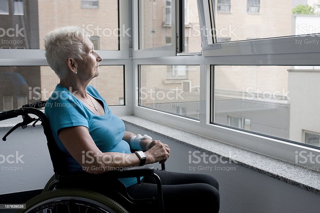 Mature woman sitting in wheelchair royalty-free stock photo