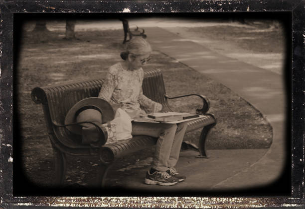 Mature woman sitting on a park bench while sketching the scene stock photo