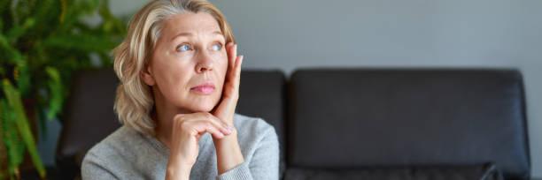 Mujer madura sentada en un sofá blanco en una casa tocándose la cabeza con las manos mientras tiene dolor de cabeza - foto de stock