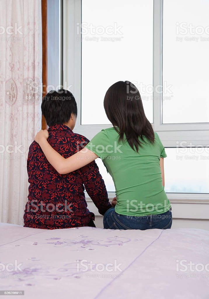 Mature woman sitting on bed with young woman stock photo