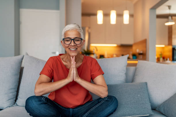 mature woman sitting on couch doing yoga exercises at home - meditation stock pictures, royalty-free photos & images