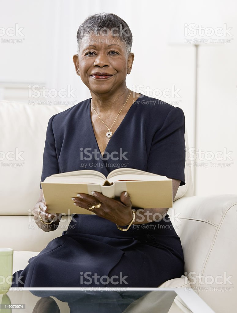 Mature Woman Sitting on Couch With Book royalty-free stock photo