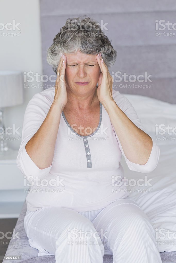 Mature woman sitting on her bed has headache royalty-free stock photo