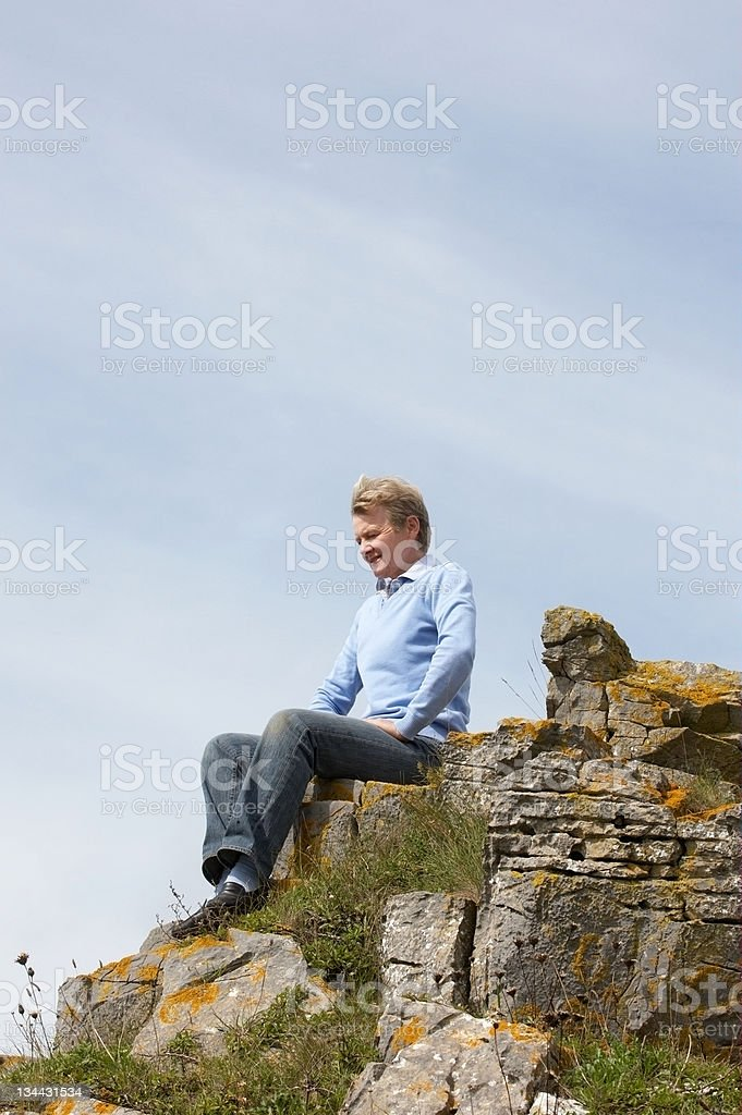 Mature woman sitting on rocky clifftop royalty-free stock photo