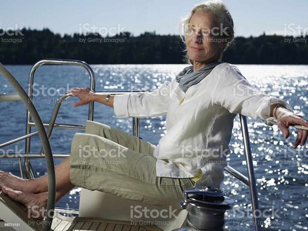 Mature woman sitting on sailboat royalty-free stock photo