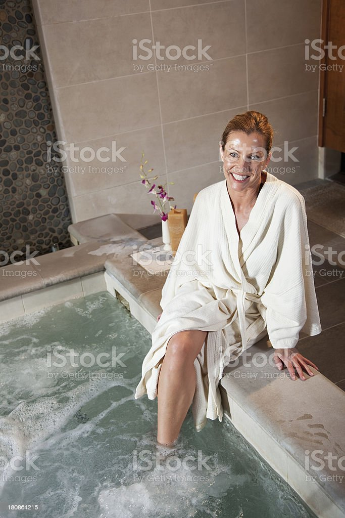 Mature woman sitting on side of jacuzzi stock photo