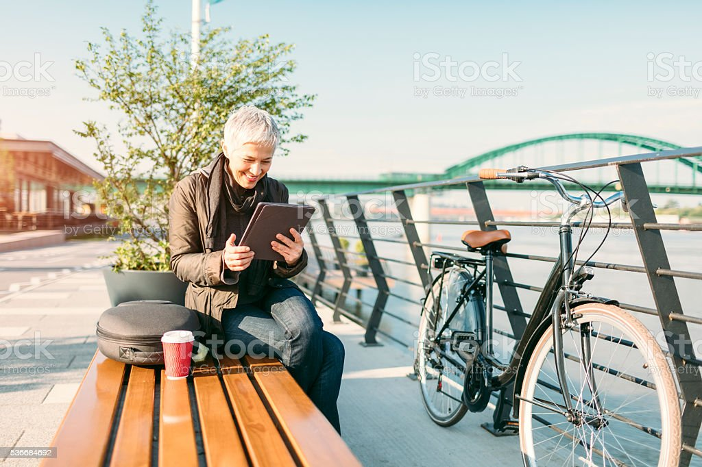 Mature Woman Sitting, Using Tablet And Drinking Coffee. stock photo