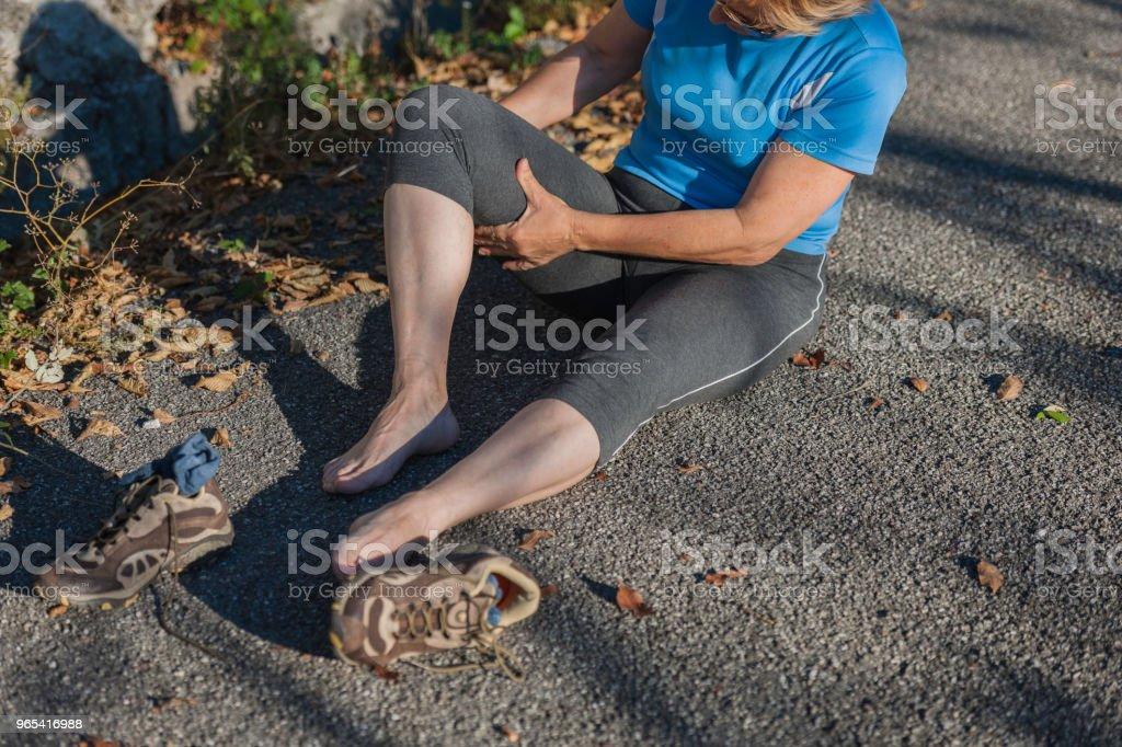 Mature woman sitting,runner looks injured leg,Italy,Europe zbiór zdjęć royalty-free