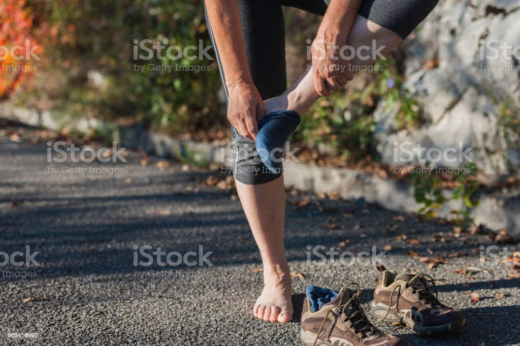 Mature woman sitting,runner looks injured leg,Italy,Europe zbiór zdjęć royalty-free