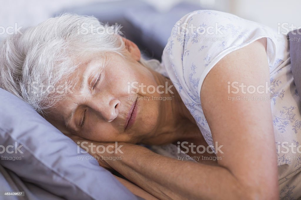 Mature woman sleeping in her bed stock photo