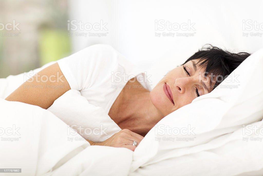 mature woman sleeping on bed stock photo