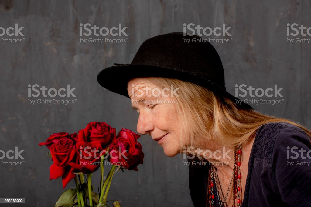 Mature woman smells dying roses.She closes her eyes for inspiration or is it prayer? royalty-free stock photo