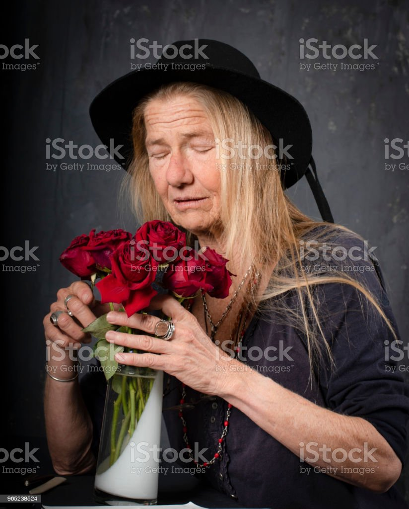 Mature woman smells dying roses.She closes her eyes for inspiration or is it prayer? zbiór zdjęć royalty-free