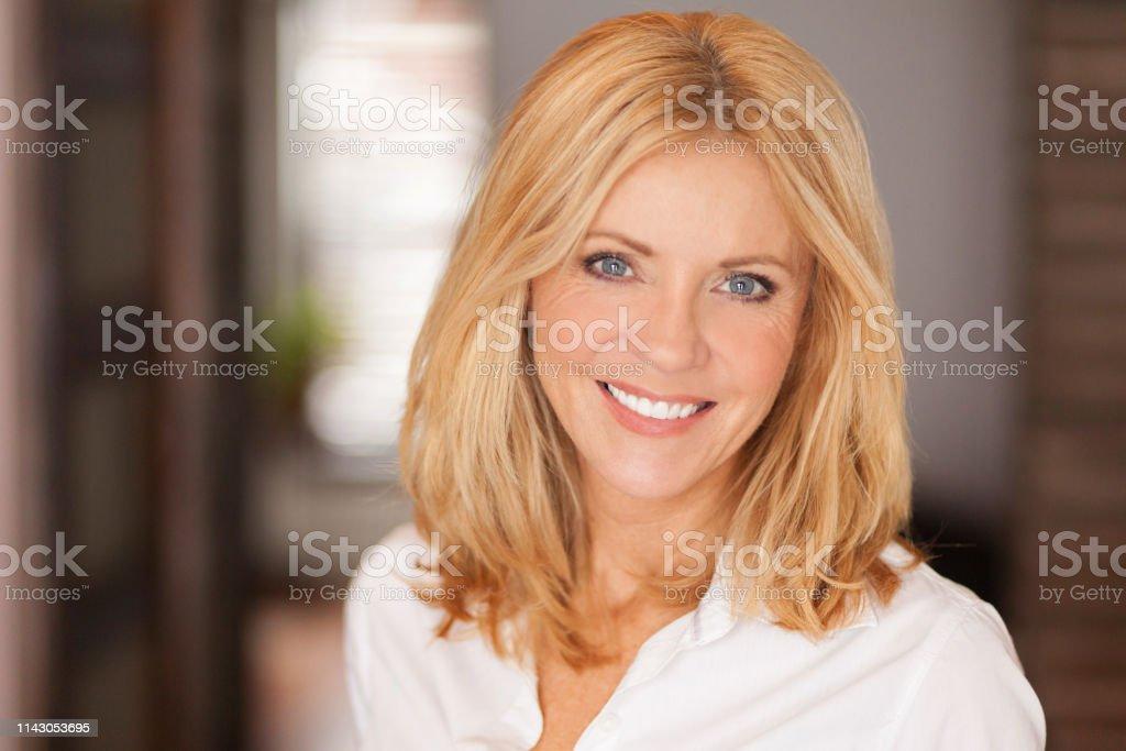 Mature woman smiling at the camera. She relaxing at home. Beautiful Mature woman smiling at the camera. She relaxing at home. Beautiful 40-44 Years Stock Photo