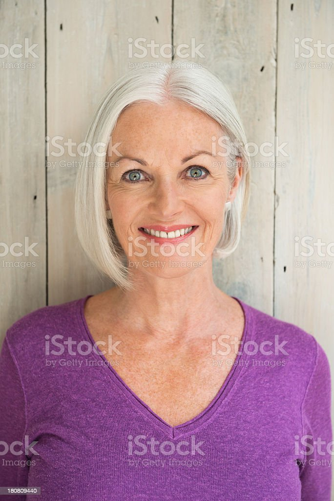 A mature woman smiling in front of a wooden wall. stock photo