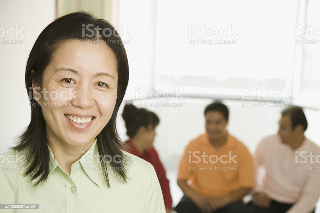 Mature woman smiling, man and women in background foto de stock libre de derechos