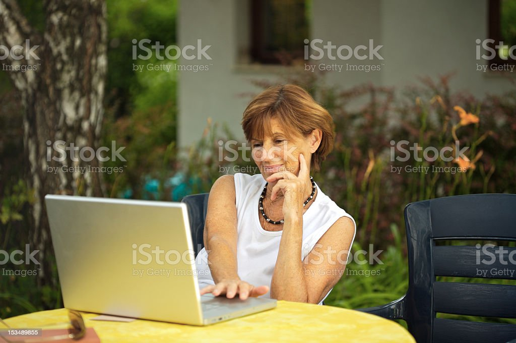 Mature woman smiling while using laptop outdoors royalty-free stock photo