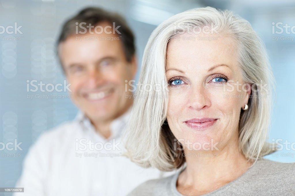 Reife Frau lächelt mit Mann im Hintergrund - Lizenzfrei 55-59 Jahre Stock-Foto