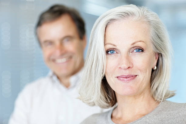 Mature woman smiling with man in the background  60 64 years stock pictures, royalty-free photos & images