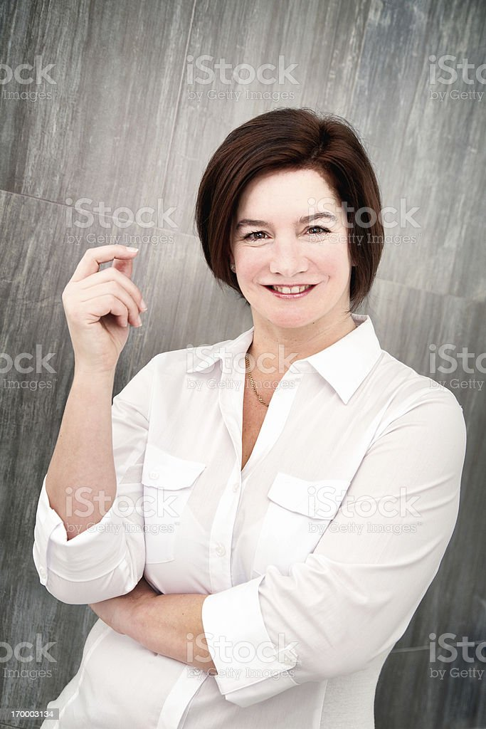 Mature woman snapping fingers in front of tile wall stock photo