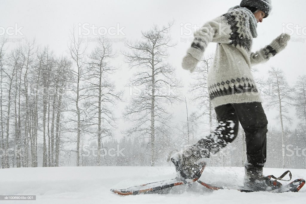 Mature woman snowshoeing royalty-free stock photo