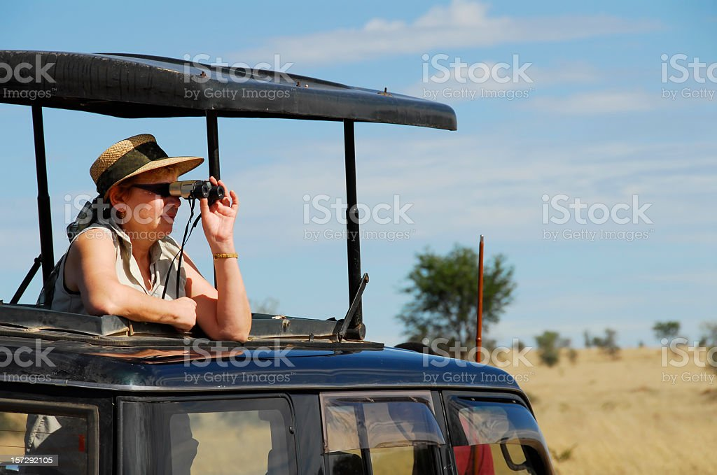 Mature woman spotting wildlife with binoculars during wildlife safari stock photo