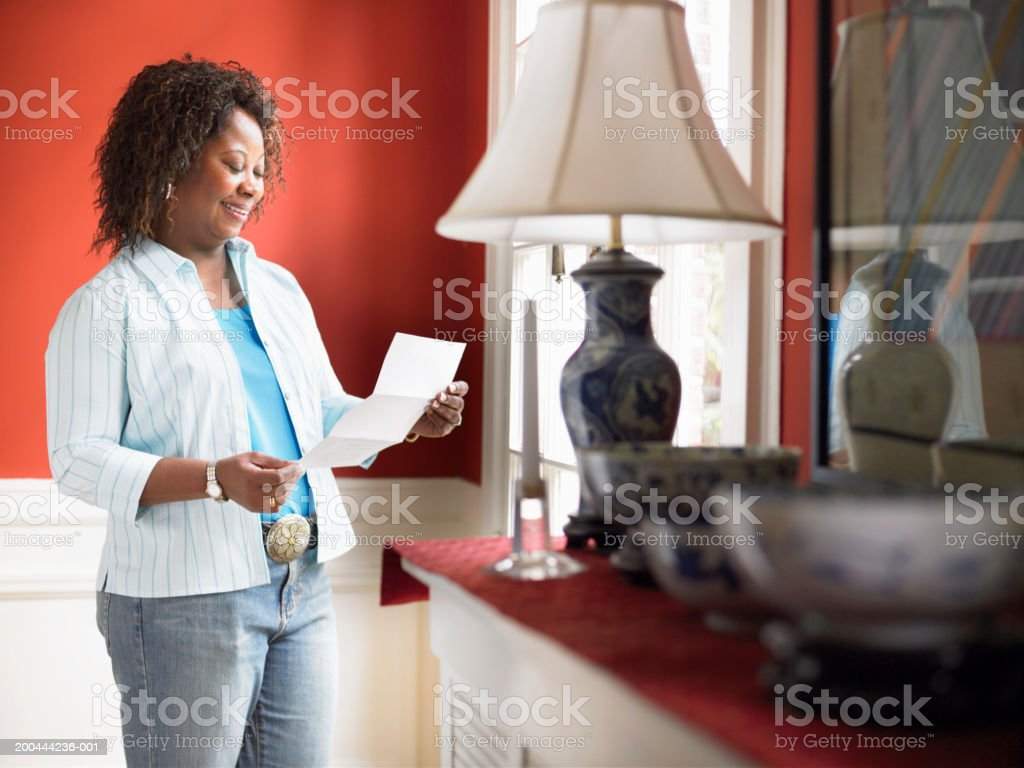 Mature woman standing by window reading mail royalty-free stock photo