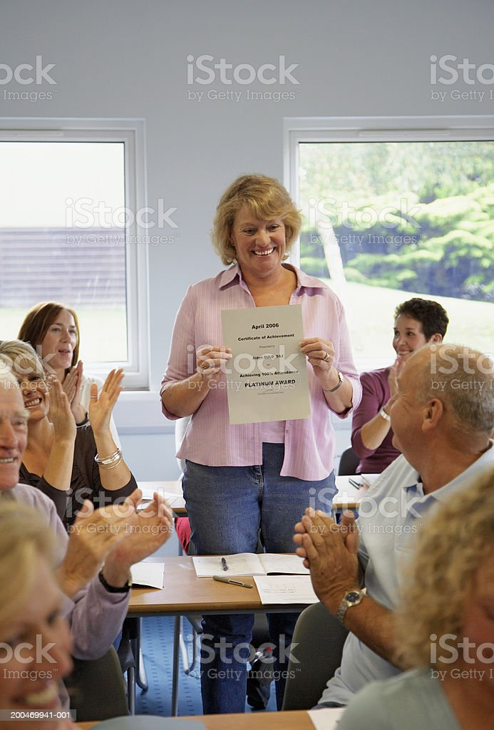 Mature woman standing in classroom holding certificate royalty-free stock photo