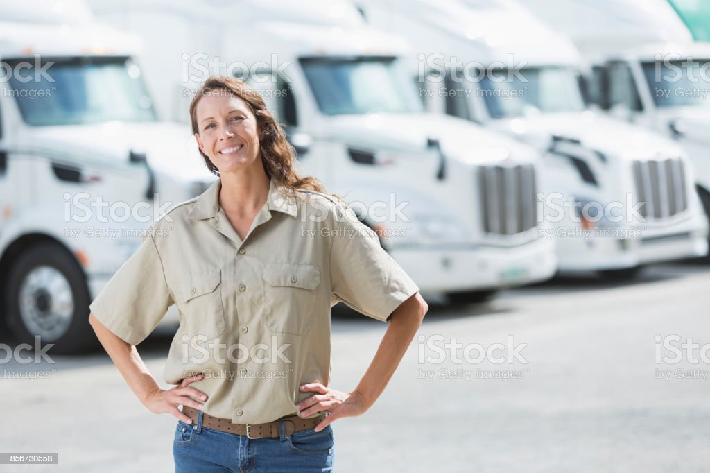 Mature woman standing in front of semi-trucks stock photo