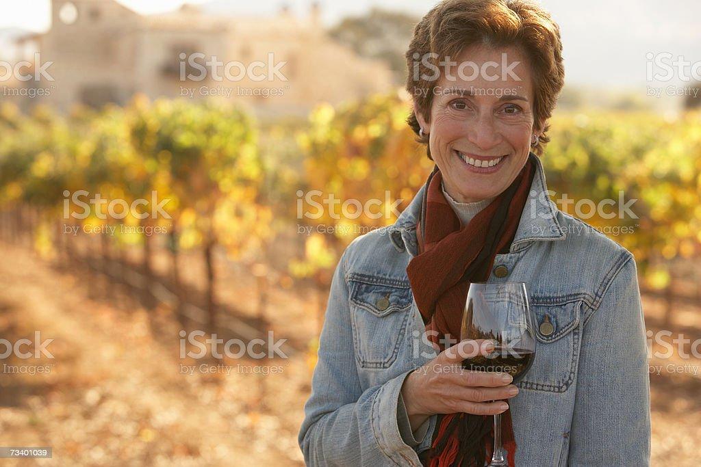 Mujer madura de pie en el Viñedo, con una copa de vino, smilin foto de stock libre de derechos