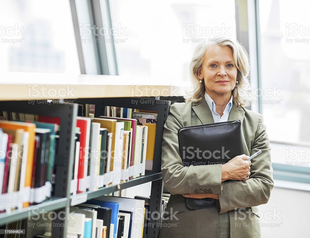 Mature woman standing next to the bookshelves. stock photo