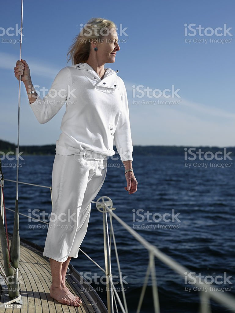 Mature woman standing on sailboat royalty-free stock photo