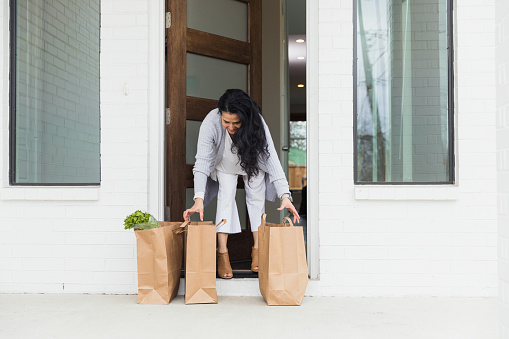 The mature adult woman steps out on her doorstep to pick up the groceries she ordered online.