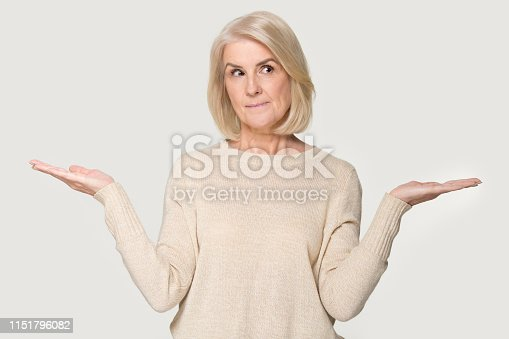 istock Mature woman stretched hands thinking makes choice on white background 1151796082