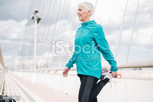 1057638814 istock photo Mature woman stretching legs 958918674