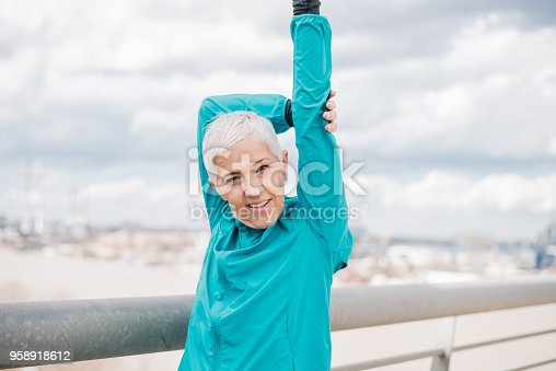 1057638814 istock photo Mature woman stretching outdoors 958918612