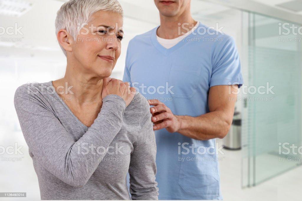 Femme d'âge mûr souffrant de maux de dos au cours de l'examen médical. Chiropratique, ostéopathie, physiothérapie. Médecine alternative, notion de soulagement de la douleur. photo libre de droits