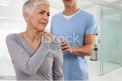 istock Mature Woman suffering from back pain during medical exam. Chiropractic, osteopathy, Physiotherapy. Alternative medicine, pain relief concept. 1126492014