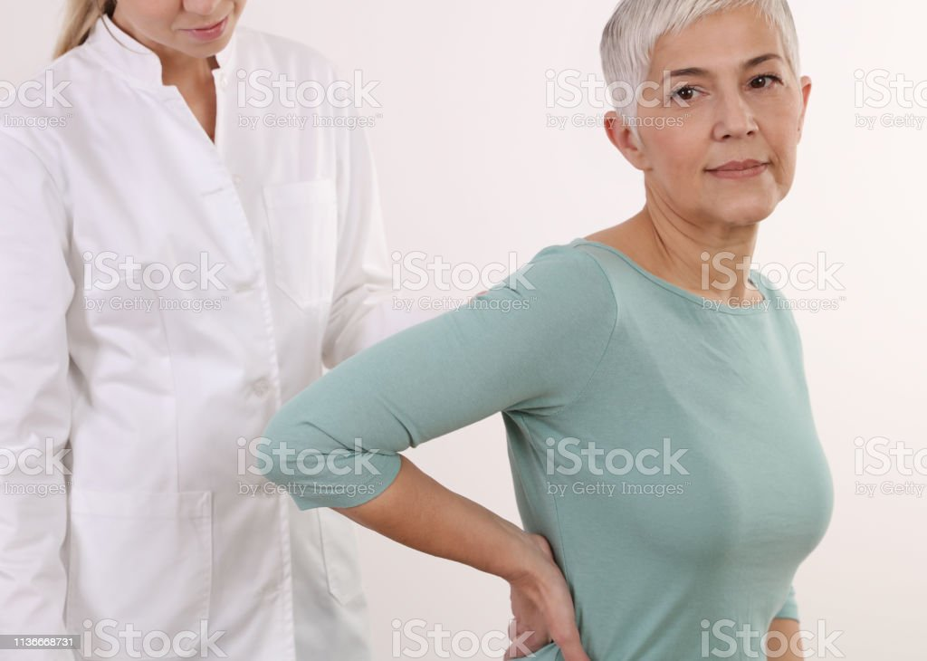 Mature Woman suffering from back pain during medical exam. Chiropractic, osteopathy, Physiotherapy. Alternative medicine, pain relief concept. stock photo