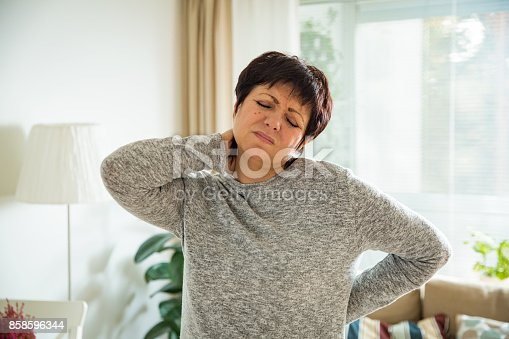istock Mature woman suffering from backache at home 858596344